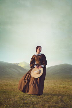 Joanna Czogala HISTORICAL WOMAN CARRYING HAT IN WINDY COUNTRYSIDE Women