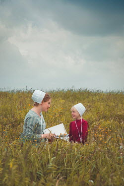 Joanna Czogala AMISH MOTHER AND DAUGHTER SITTING IN FIELD Children