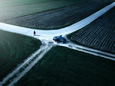 Magdalena Russocka MAN STANDING BY CAR AT CROSSROADS IN COUNTRYSIDE Men