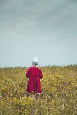 Joanna Czogala LITTLE GIRL IN BONNET STANDING IN FIELD Children