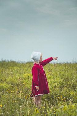 Joanna Czogala LITTLE GIRL IN BONNET POINTING IN FIELD Children