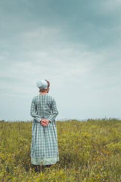 Joanna Czogala WOMAN IN BONNET AND CHECKED DRESS IN FIELD Women
