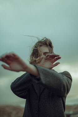 Alisa Andrei WOMAN COVERING FACE WITH ARMS IN WINDY COUNTRYSIDE Women
