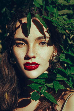 Alisa Andrei WOMAN WITH RED LIPS SURROUNDED BY GREEN LEAVES Women