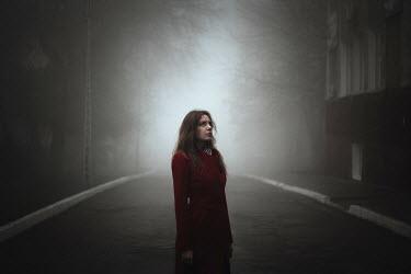 Alina Zhidovinova BRUNETTE WOMAN STANDING IN FOGGY STREET BY BUILDING Women