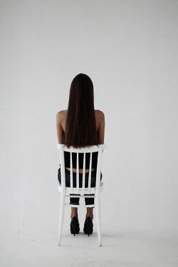 Alina Zhidovinova BRUNETTE WOMAN SITTING ON CHAIR FROM BEHIND Women