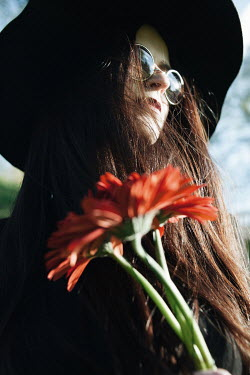 Alina Zhidovinova WOMAN IN GLASSES AND HAT CARRYING RED FLOWERS OUTDOORS Women