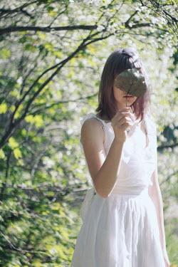 Alina Zhidovinova WOMAN WITH LEAF COVERING FACE IN SUMMERY GARDEN Women
