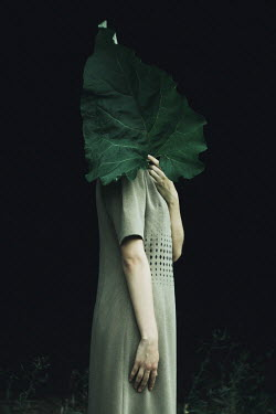 Alina Zhidovinova WOMAN STANDING WITH LEAF COVERING FACE OUTDOORS Women