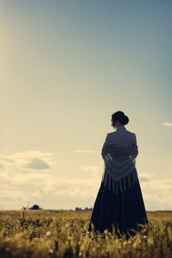 Magdalena Russocka historical woman standing in countryside at sunset