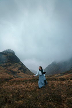 Rekha Garton WOMAN WALKING IN COUNTRYSIDE WITH MISTY HILLS Women