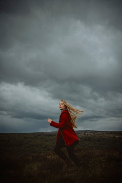 Shelley Richmond BLONDE WOMAN RUNNING IN STORMY COUNTRYSIDE Women