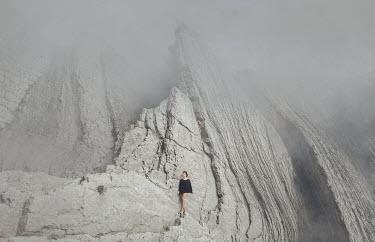 Alisa Andrei WOMAN STANDING ON STEEP MOUNTAIN IN MIST Women