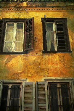 Irene Lamprakou WEATHERED EXTERIOR OF OLD HOUSE WITH SHUTTERS Houses