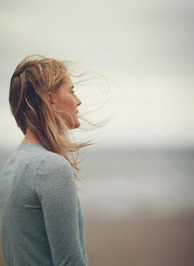 Mark Owen BLONDE WOMAN STANDING ON BREEZY BEACH Women