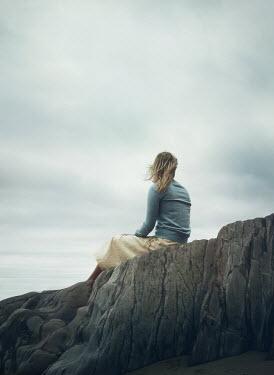 Mark Owen BLONDE WOMAN SITTING ON ROCK WATCHING SEA Women
