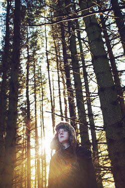 Catherine Macbride Teenage girl in fur hat in forest during sunset