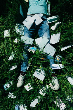 Giovan Battista D'Achille Legs of dead young man in grass with envelopes and post cards