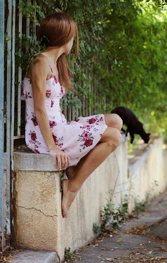 Irene Lamprakou Young woman in floral dress sitting on wall by cat