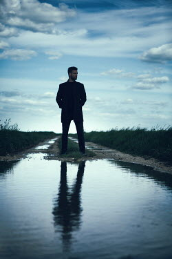 Magdalena Russocka modern man reflected in puddle on country road