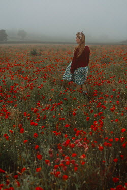 Shelley Richmond Young woman in vintage clothing standing in poppy field