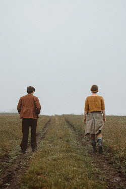 Shelley Richmond Young couple in vintage clothing walking in field