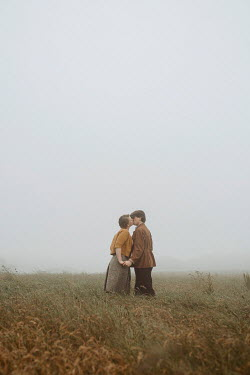 Shelley Richmond Young couple in vintage clothing kissing in field