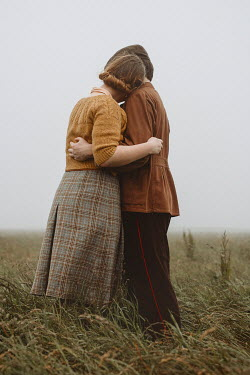 Shelley Richmond Young couple in vintage clothing embracing in field