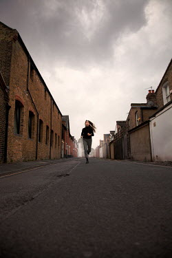 Miguel Sobreira Young woman running on road between houses
