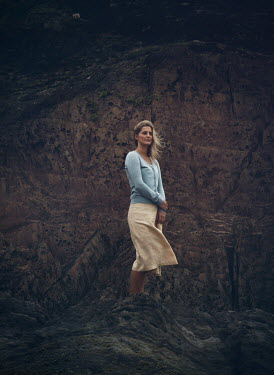 Mark Owen Young woman standing on rock at beach
