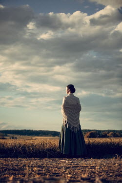 Magdalena Russocka historical woman standing in field at sunset