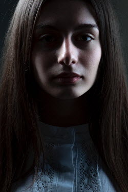 Magdalena Russocka close up of teenage girl staring in shadowy room