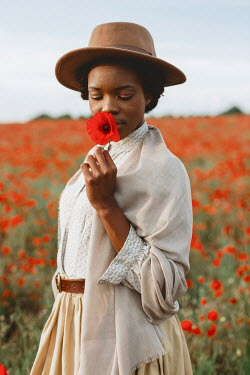 Shelley Richmond Young African woman with historical clothing in poppy field