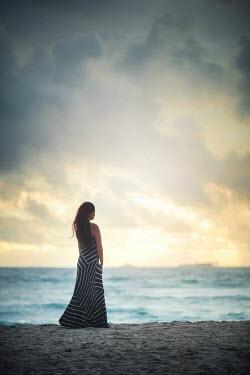 Evelina Kremsdorf WOMAN IN STRIPY DRESS WATCHING SEA WITH SUNSET Women