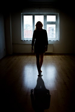 Valentino Sani WOMAN WALKING INSIDE URBAN APARTMENT IN SHADOW Women