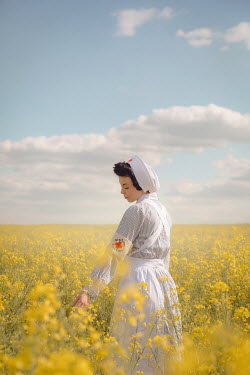 Joanna Czogala SAD NURSE IN FIELD OF YELLOW FLOWERS Women