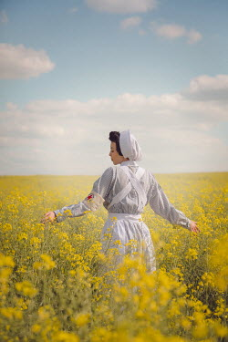 Joanna Czogala NURSE STANDING IN FIELD OF YELLOW FLOWERS Women