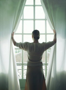 Mark Owen WOMAN OPENING CURTAINS AND WATCHING GRAND GARDEN Women