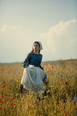 Magdalena Russocka young historical maid walking in field with wild flowers