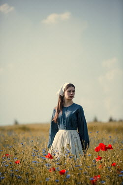 Magdalena Russocka young historical maid standing in field with wild flowers