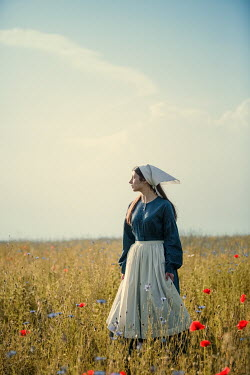 Magdalena Russocka young maid standing in field with wild flowers
