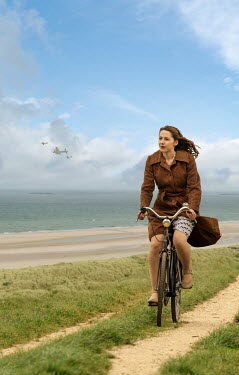 CollaborationJS WOMAN IN COAT CYCLING ON PATH BY SEA Women