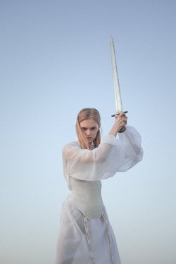 Inna Mosina WOMAN IN WHITE HOLDING SWORD OUTDOORS Women