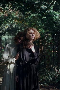 Irina Orwald TWO WOMEN STANDING IN GARDEN ARBOR Women