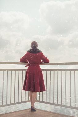 Joanna Czogala BRUNETTE WOMAN IN COAT WATCHING SEA WITH SNOW Women