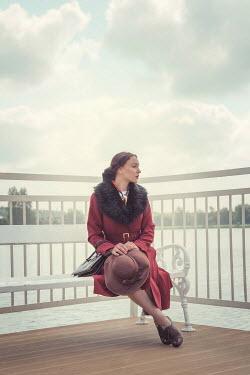 Joanna Czogala WOMAN IN COAT SITTING BY RIVER HOLDING HAT Women