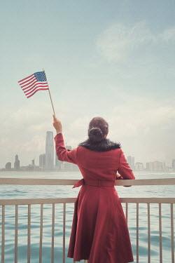 Joanna Czogala WOMAN WAVING AMERICAN FLAG WATCHING CITY BY WATER Women