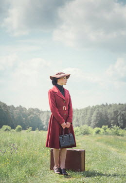 Joanna Czogala WOMAN WITH HAT AND SUITCASE STANDING IN COUNTRYSIDE Women