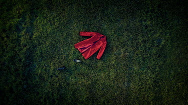 Mary Wethey RED COAT AND BLACK SHOES LYING ON GRASS Miscellaneous Objects