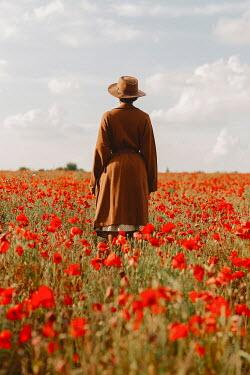 Shelley Richmond WOMAN IN HAT STANDING IN POPPY FIELD Women